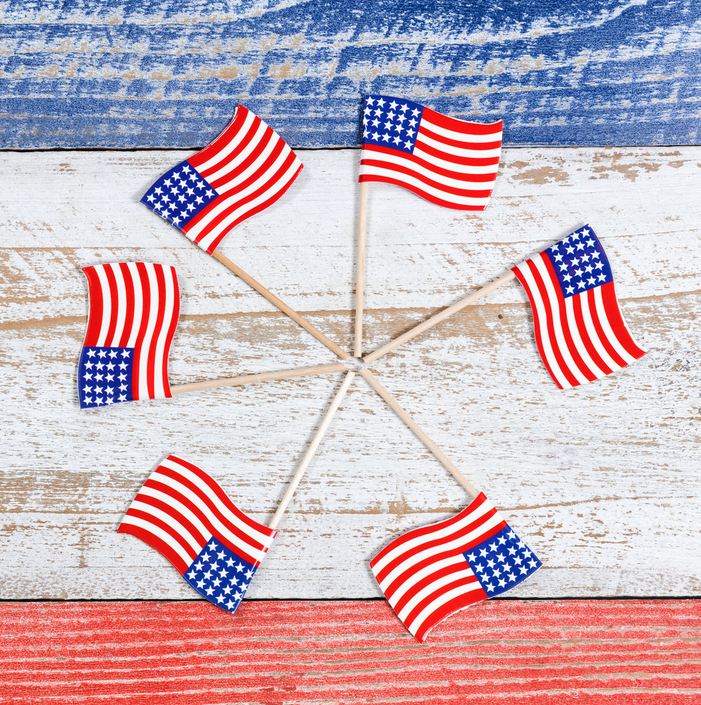 Hot glue small wooden flags in a circle for an easy and patriotic wreath!  Here are some darling ideas for 4th of July DIY door wreaths. You will love them!
