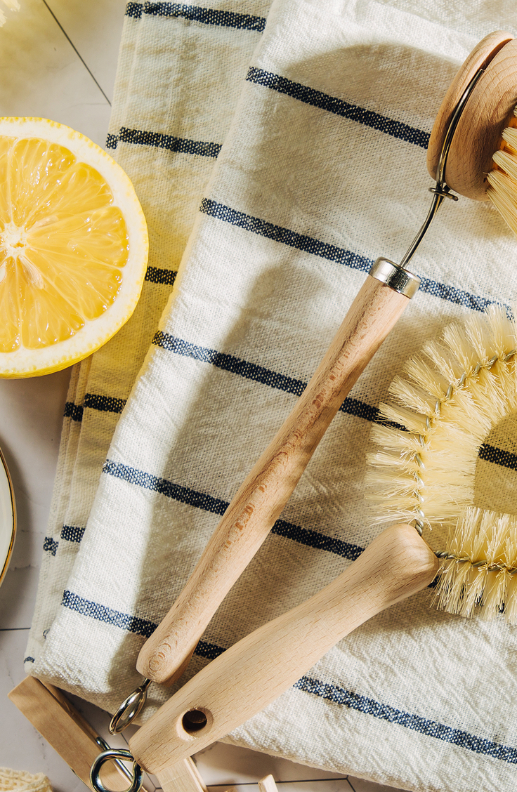 Kitchen Cleaning Hacks. A striped dish towel, with a lemon and scrub brushes.