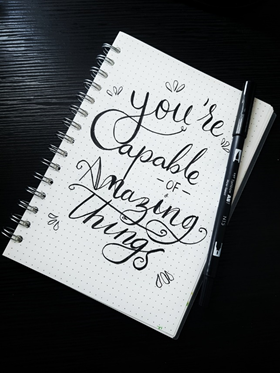 A notebook with a positive mantra written on it - your past doesn't define you.