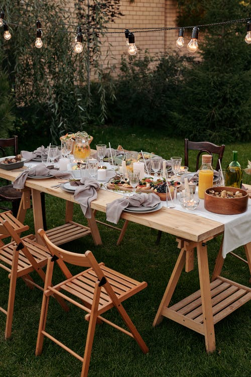 outdoor furniture in a garden with string lights